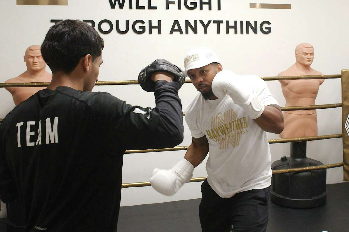 After a pandemic-related layoff from a corporate human resources position in May 2020, Justin Rogers, right, charted a course as as fitness trainer that led to a job as manager of the new Mayweather Boxing + Fitness gym in Pearland. Boxing instructor Robert Gonzalez and Rogers demonstrate a typical training session.