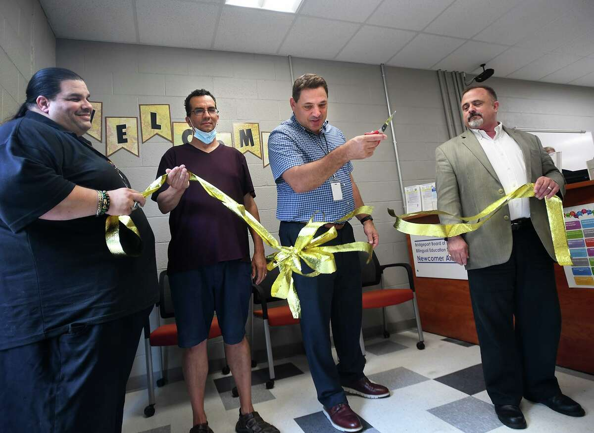 Bridgeport Superintendent of Schools Michael Testani cuts the ribbon on the Board of Education's Newcomer Arrival Center at Central High School in Bridgeport, Conn. on Tuesday, August 10, 2021. From left are board members Albert Benejan Grajales, Joe Sokolovic, Testani, and John Weldon.
