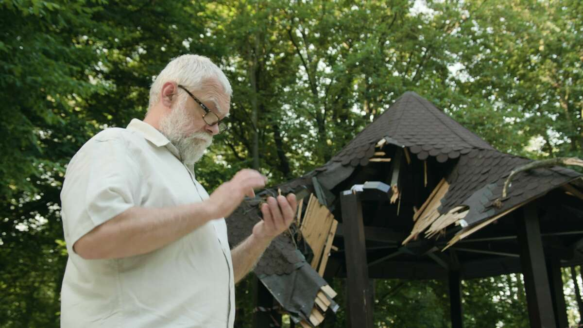 A man talking on the phone outdoors in front of a broken arbor.