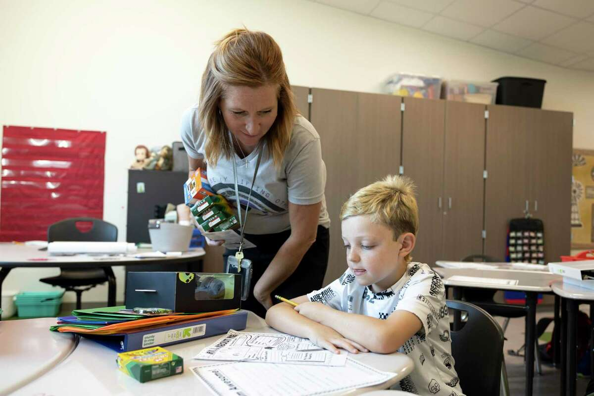 Nichole Slott, third grade teacher, left, assists Lukas Grimm with an assignment during the first day of school at Eddie Ruth Lagway Elementary, Wednesday, Aug. 11, 2021, in Conroe. The 101,930 square foot two-story building will house 850 kindergarten through fifth grade students.