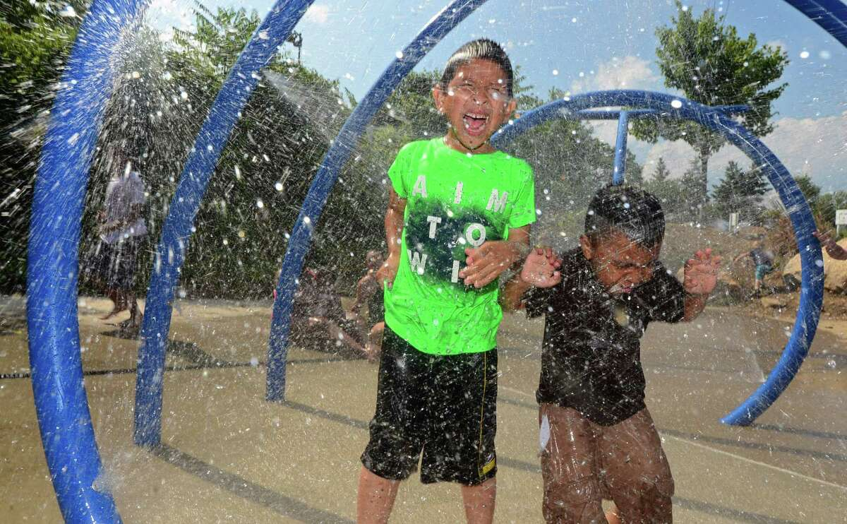 FILE PHOTO: In 2016, Jeremy Orrellanes and Angel Orellanes beat the heat by playing at the splash park in Devon's Playground in Norwalk.