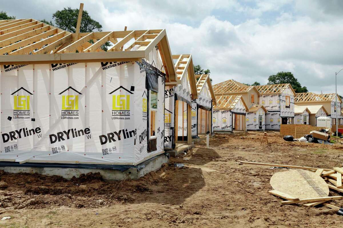 Construction workers build homes for LGI Homes in a new section of the Bauer Landing subdivision in Hockley.