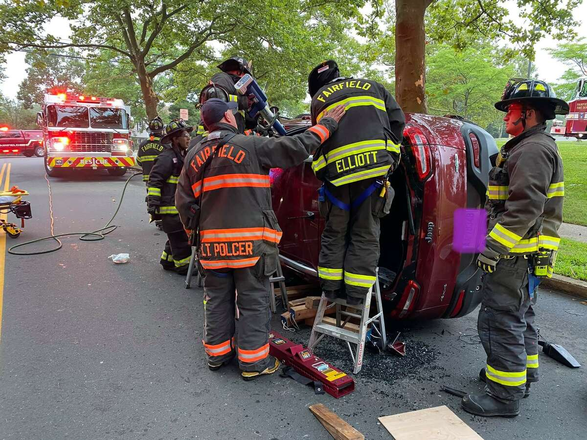 Fire crews working the scene of a rollover in Fairfield, Conn., on Tuesday, Aug. 10, 2021. Edits to the vehicle's license plate were not made by Hearst Connecticut Media.