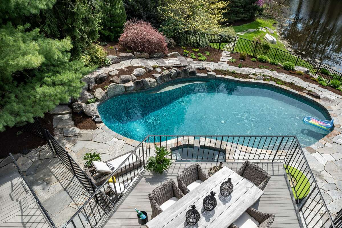 The Hemlock Hill Road homehas a heated pool and spa, as well as an upper-level deck and walkout lower level patio.