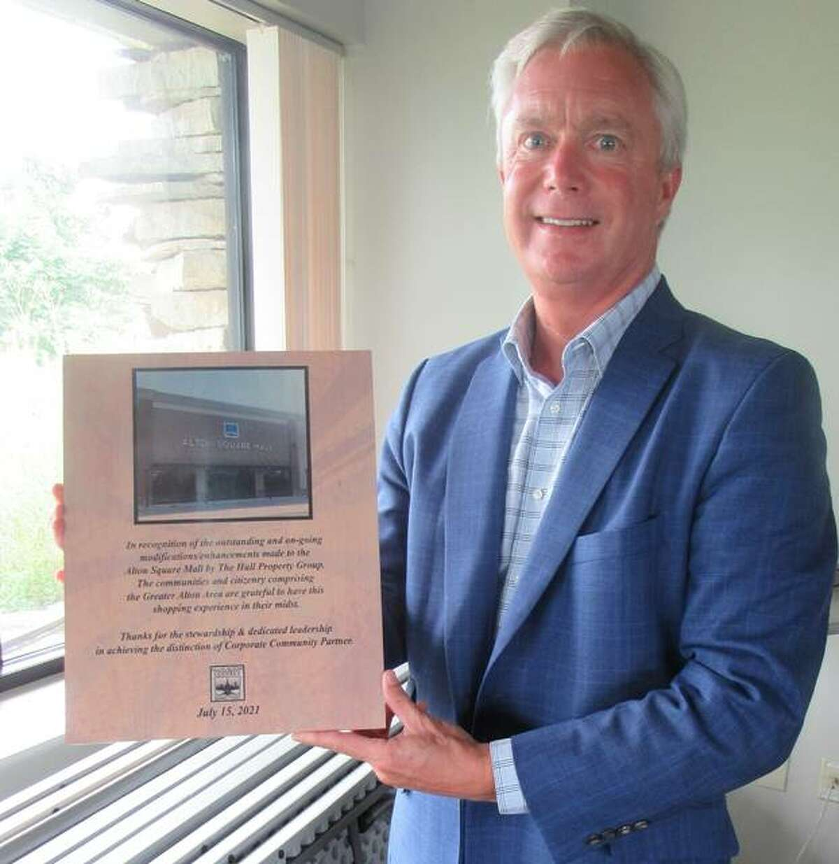 John Mulherin, Vice President of Government Relations, of Hull Property Group, displays a plaque presented to the group by the North Alton Godfrey Business Council. Based in Augusta, Georgia, the firm bought the mall in 2015 and has invested millions in improvements to it. - Dylan Suttles The Telegraph