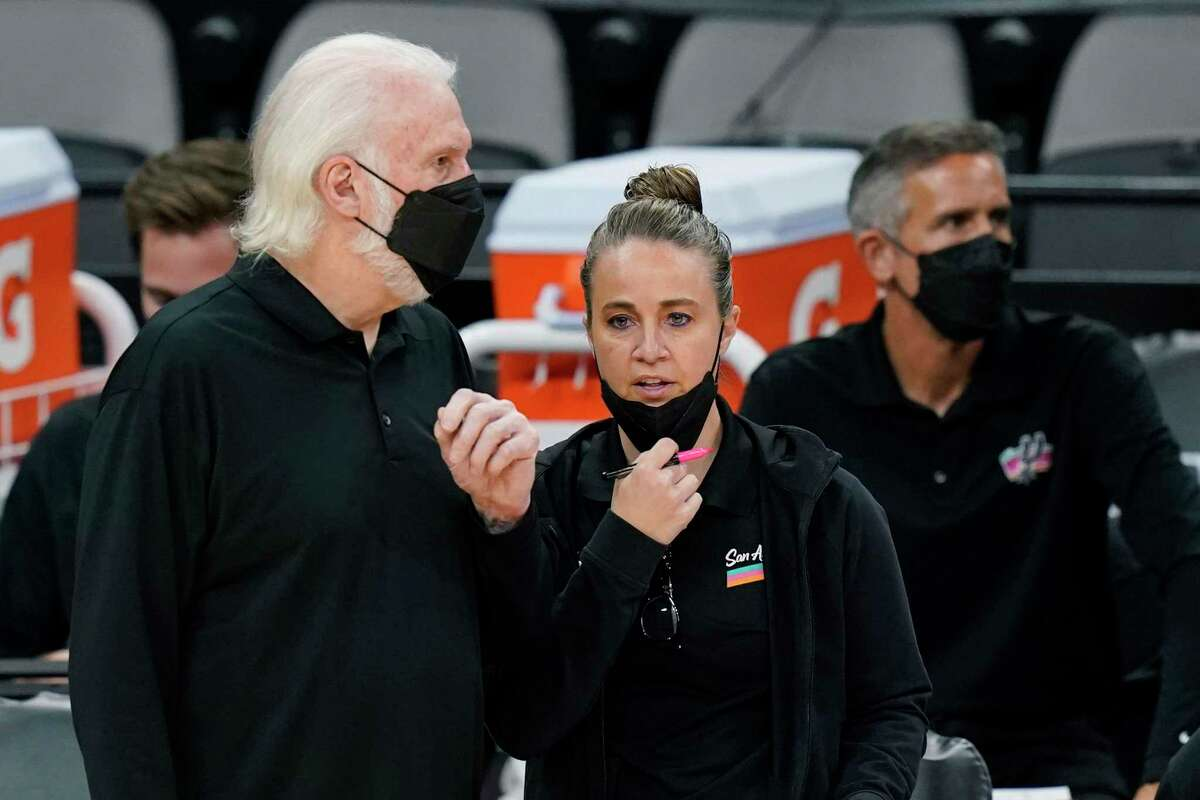 San Antonio Spurs head coach Gregg Popovich, left, talks with assistant coach Becky Hammon during the second half of an NBA basketball game against the Orlando Magic in San Antonio, in this Friday, March 12, 2021, file photo. Hammon can't wait for the time when it's the norm for females to interview for head coaching positions in the NBA and their gender isn't the story. Hammon's entering her eighth season as an assistant and has been interviewed for several head coach positions but hasn't gotten an offer yet to be the first female to lead a NBA team. (AP Photo/Eric Gay, File)