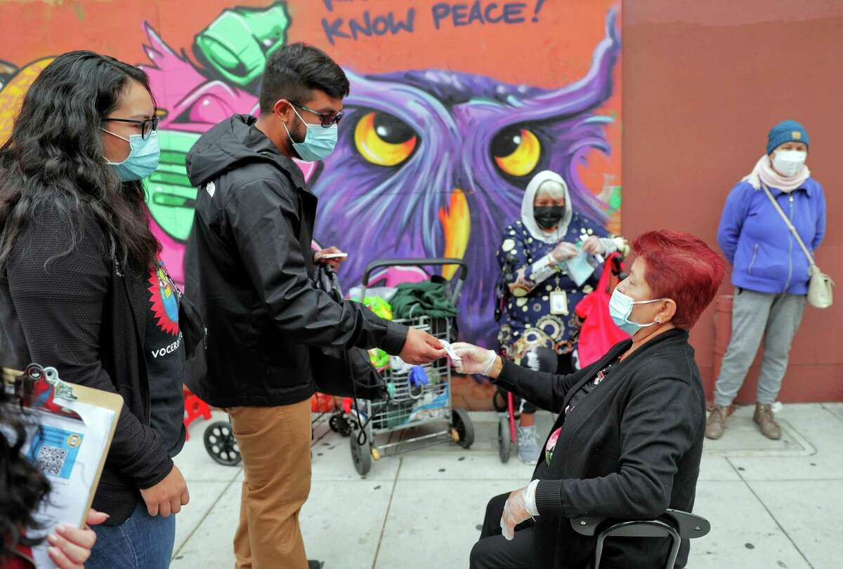 Efrain Trujillo, center, hands a sticker to Rosa Rangel, who was already vaccinated, as he and other ambassadors help local residents with vaccination resources outreach in the Fruitvale district of Oakland, Calif., on Thursday, August 5, 2021. As the DELTA variant surges in California, Latinos continue to suffer disproportionately. A new effort by the Unity Council and UCSF is targeting the Fruitvale district to bring vaccine information to residents.