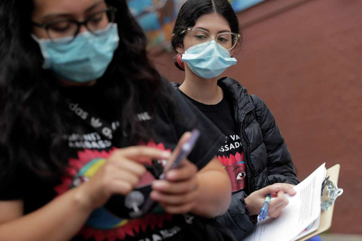 Carolina Quintero watches as Raquel Marquez looks up a vaccination site for Evangelina Nieves while they help local residents with vaccination resources in the Fruitvale district of Oakland in August. Employees of the city of Oakland would be required to get vaccines by mid-October under a new proposal..