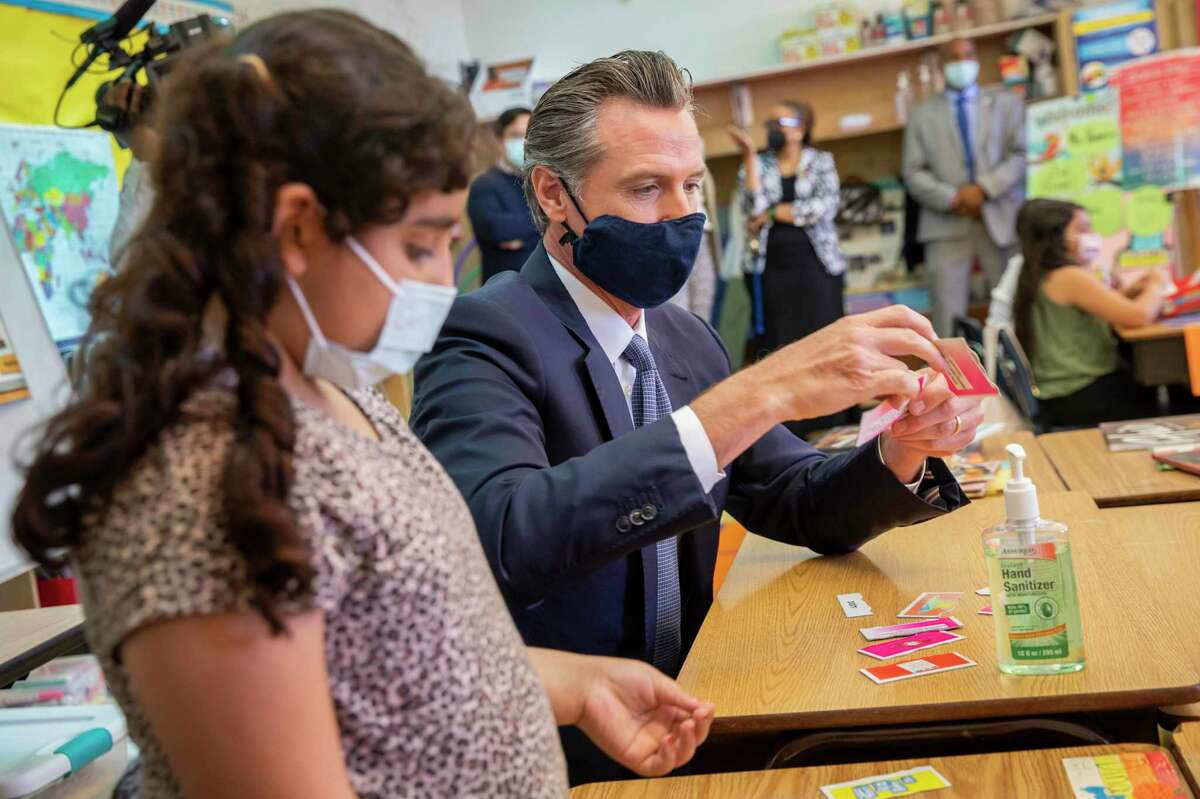 From left: Dina Kassan talks with California Gov. Gavin Newsom, who visited Carl B. Munck Elementary School, Wednesday, Aug. 11, 2021, in Oakland, Calif. The governor announced that California will require its 600,000 teachers and school employees to be vaccinated against the novel coronavirus or submit to weekly COVID-19 testing.