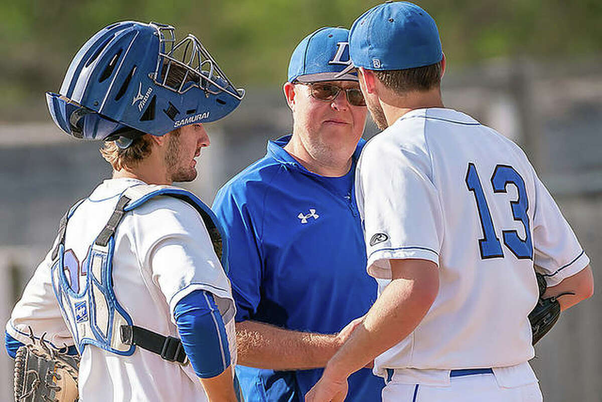 Lewis and Clark assistant baseball coach Alex Ferguson, center, meets with pitcher Brock Seymour (13) and catcher Jacob Sutton during a game last season in Godfrey. Ferguson is the interim head coach of the Trailblazers, following the retirement of longtime coach Randy Martz.