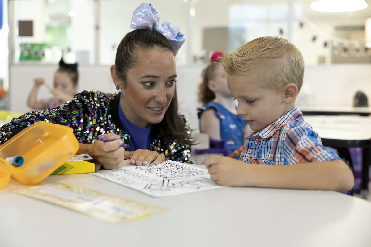 Shannon Grimm, kindergarten teacher, left, assists Joshua Morris with a coloring assignment during the first day of school at Eddie Ruth Lagway Elementary, Wednesday, Aug. 11, 2021, in Conroe. The 101,930 square foot two-story building will house 850 kindergarten through fifth grade students.