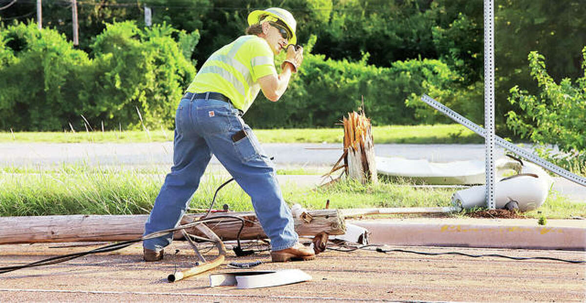An Ameren worker disconnects power from a downed light pole Wednesday morning after it was struck by a motorist. John Badman The Telegraph