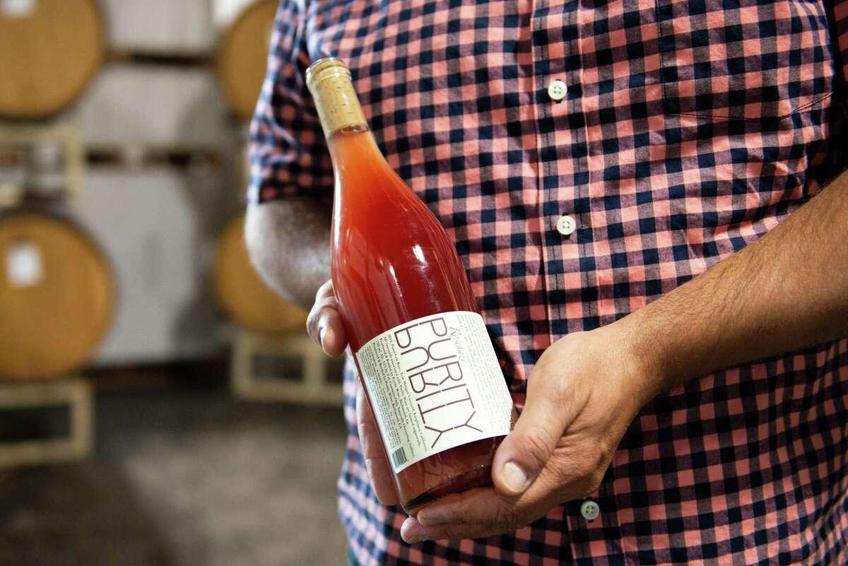 Noel Diaz, winemaker of Purity Wines, holding a bottle in his tasting room in Richmond.