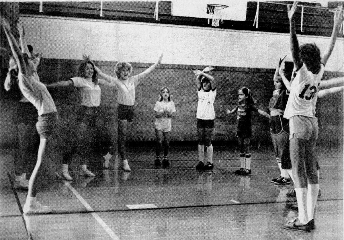 """""""Come on, get those arms out!"""" instructs one of the Manistee High School varsity cheerleaders as the cheerleading clinic for girls in grades four through six opens at the junior high gym. The clinic, which is being put on by the MHS varsity cheerleaders, is designed to teach new chants, jumps and other cheerleading basics. The photo was published in the News Advocate on Aug. 13, 1981. (Manistee County Historical Museum photo)"""