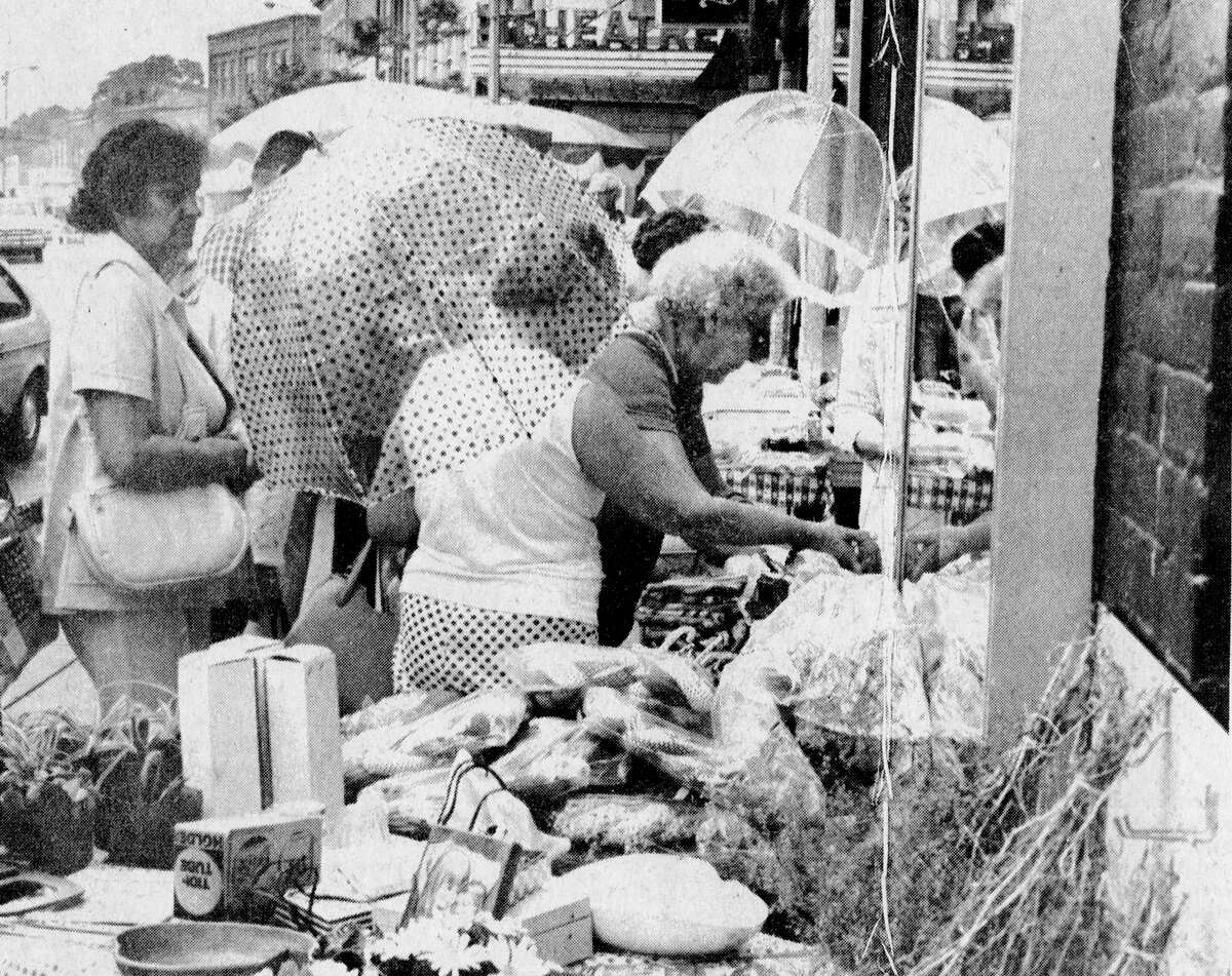 Shrugging off the inclement weather - with the aid of their umbrellas - these women had an enjoyable time browsing through the ethnic baked goods and other items on sale on River Street as part of Manistee's annual International Days festivities. The photo was published in the News Advocate on Aug. 14, 1981. (Manistee County Historical Museum photo)