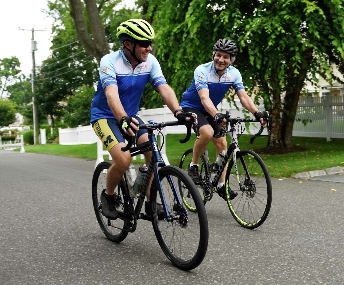 Jamie Meehan, left, Alec Fraser, ride their bikes in Old Greenwich, Conn. Wednesday, Aug. 4, 2021. Fraser lost his son, Julian, to cancer in 2017, and will be riding his bike across the country with Meehan later this month to raise money for cancer research.