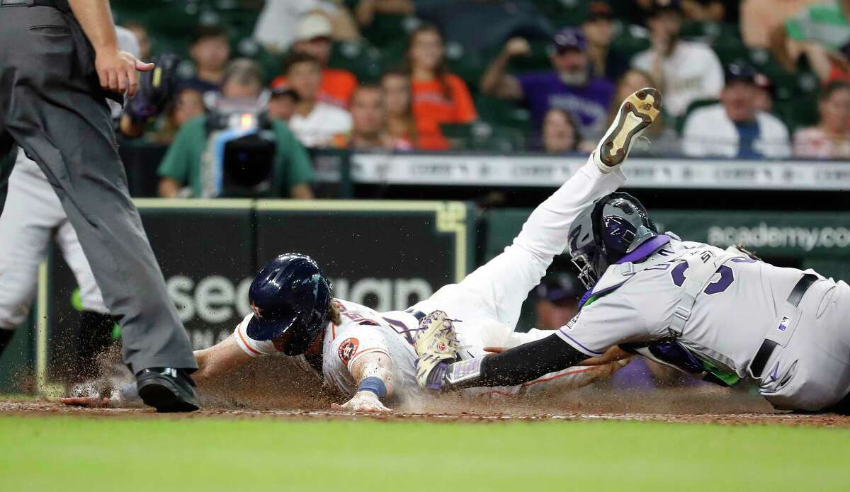 Houston Astros Jake Meyers (6) beats the tag (on an overturned call) from Colorado Rockies catcher Elias Diaz (35) as he scored a run on a sac fly by Martin Maldonado during the sixth inning at Minute Maid Park, Wednesday, August 11, 2021, in Houston.