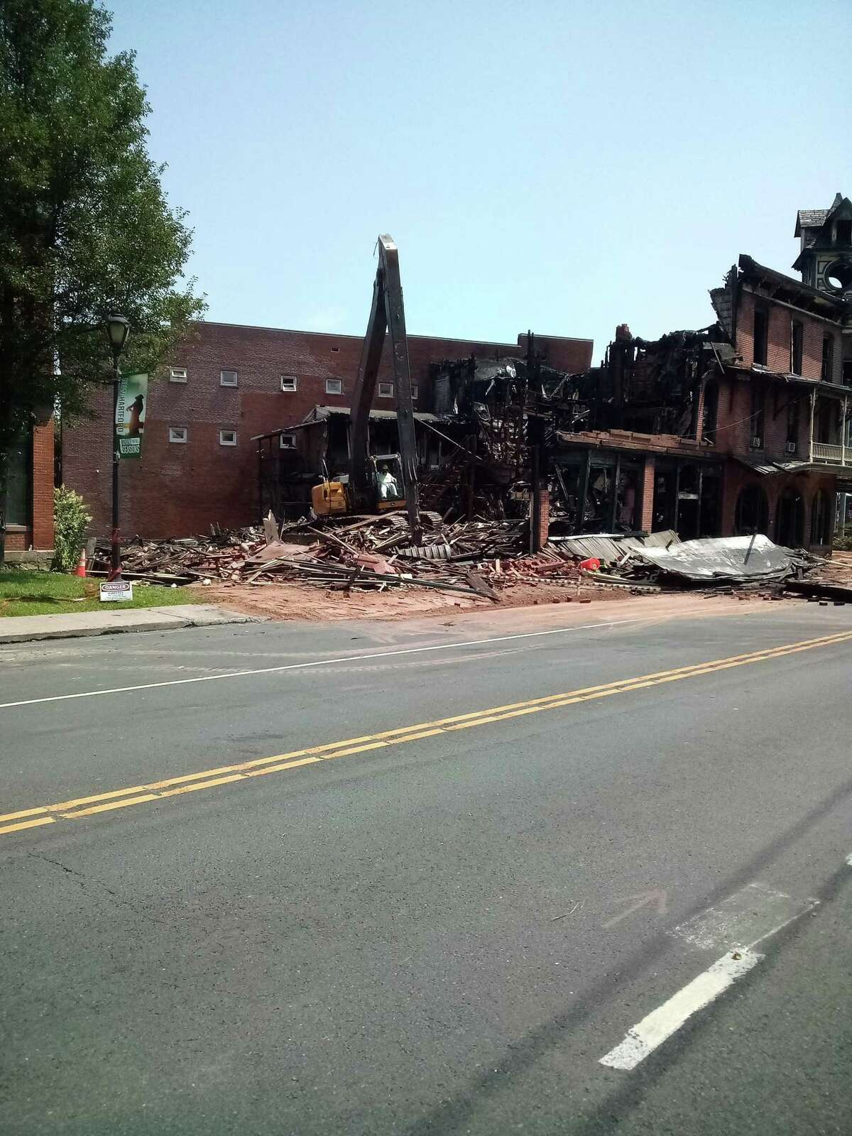 The New Hartford House was demolished Wednesday after it was severely damaged by a three-alarm fire Tuesday. A member of Environmental Solutions mans a bulldozer at the site, crushing debris.