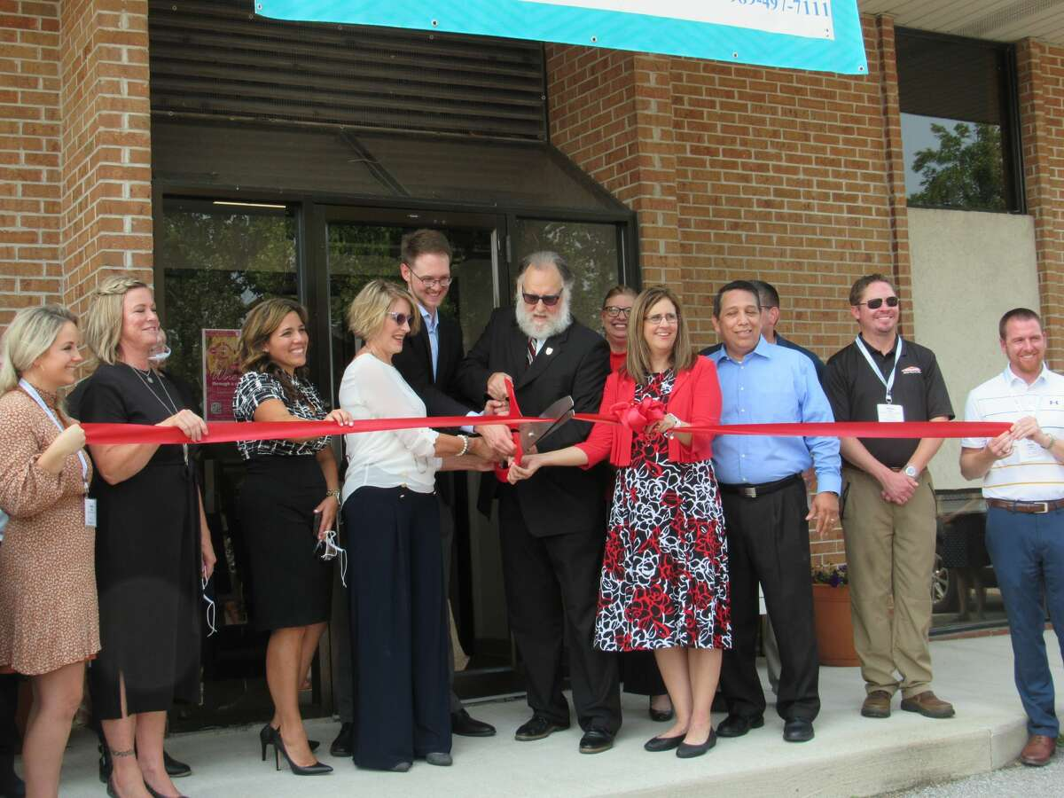 Staff members of VOICEInc. and the Midland Business Alliance participate in a ribbon-cutting ceremony Wednesday, Aug. 11.