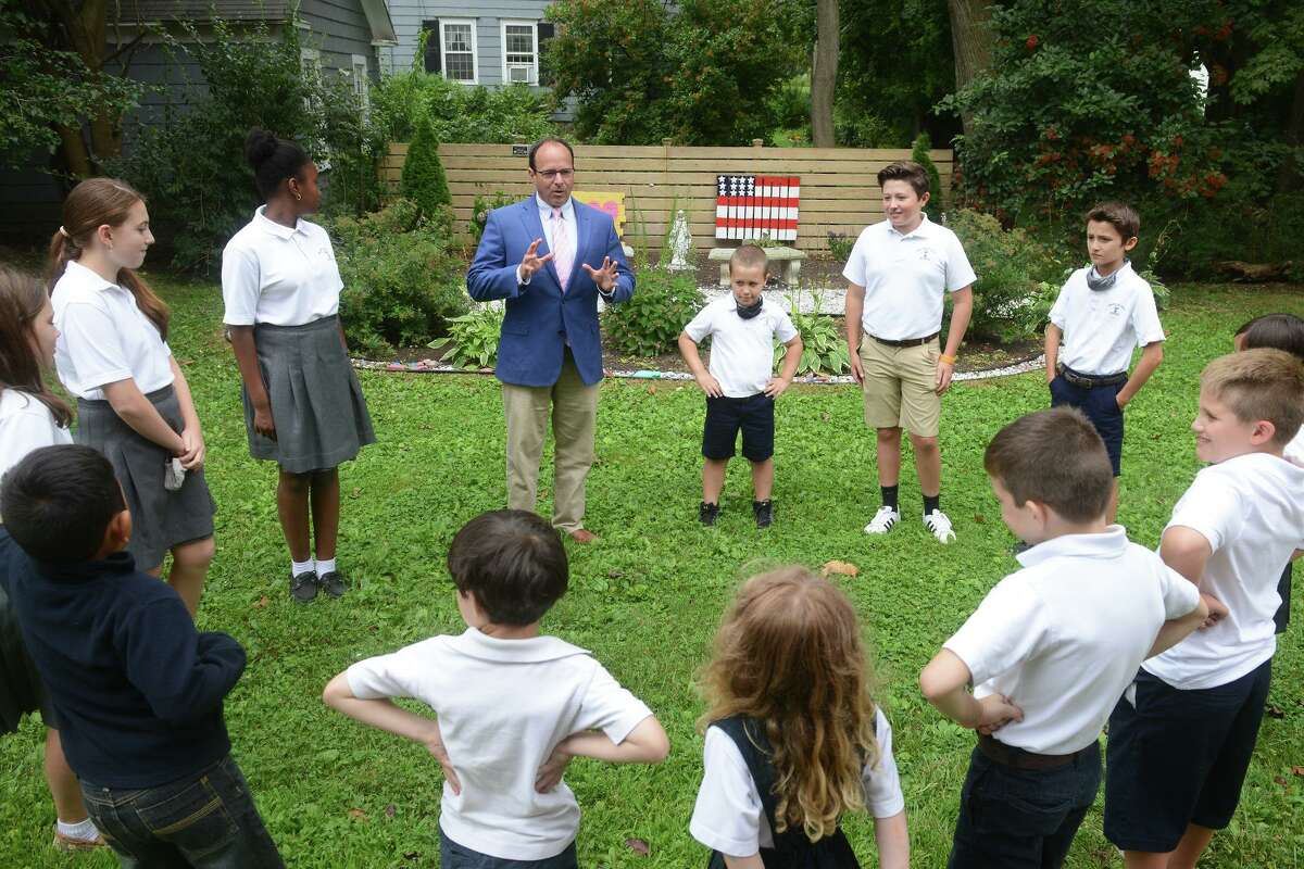 Christopher Robertson, the new Principal at St. James School, meets with some of his students in Stratford, Conn. Aug. 5, 2021.