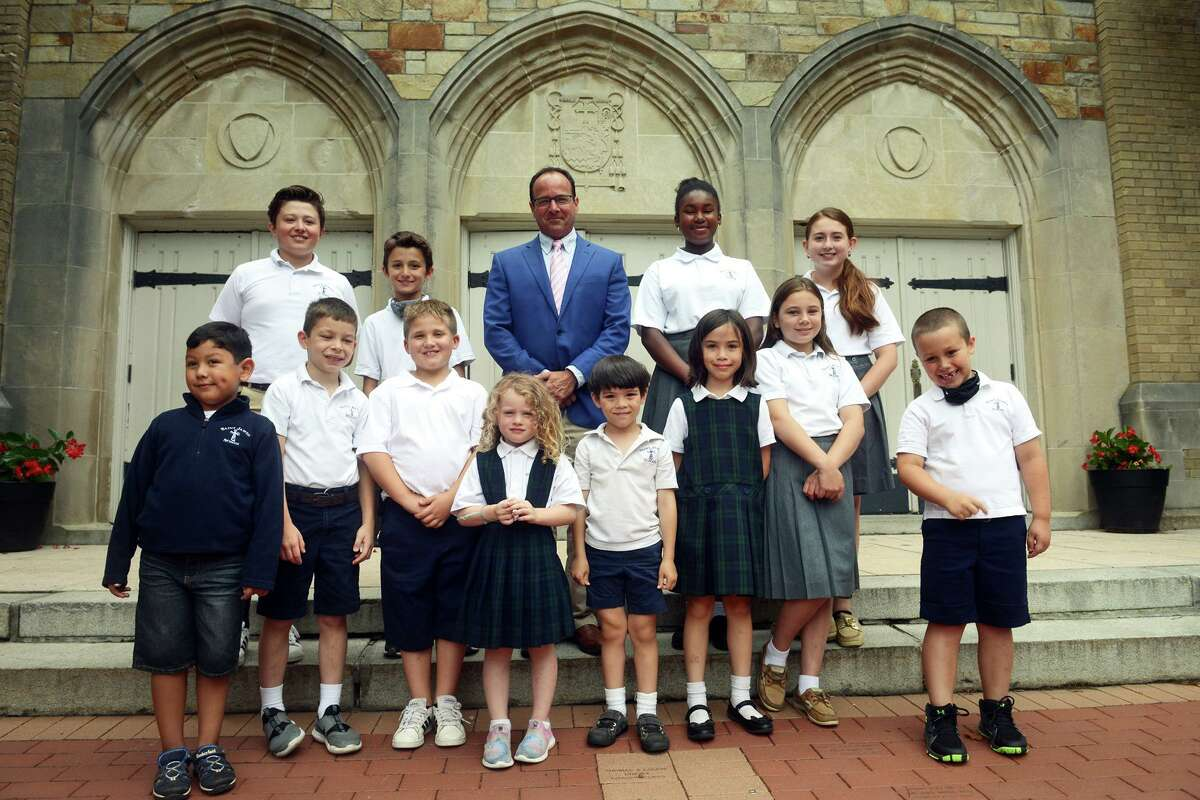 Christopher Robertson, the new Principal at St. James School, poses with some of his students in Stratford, Conn. Aug. 5, 2021.