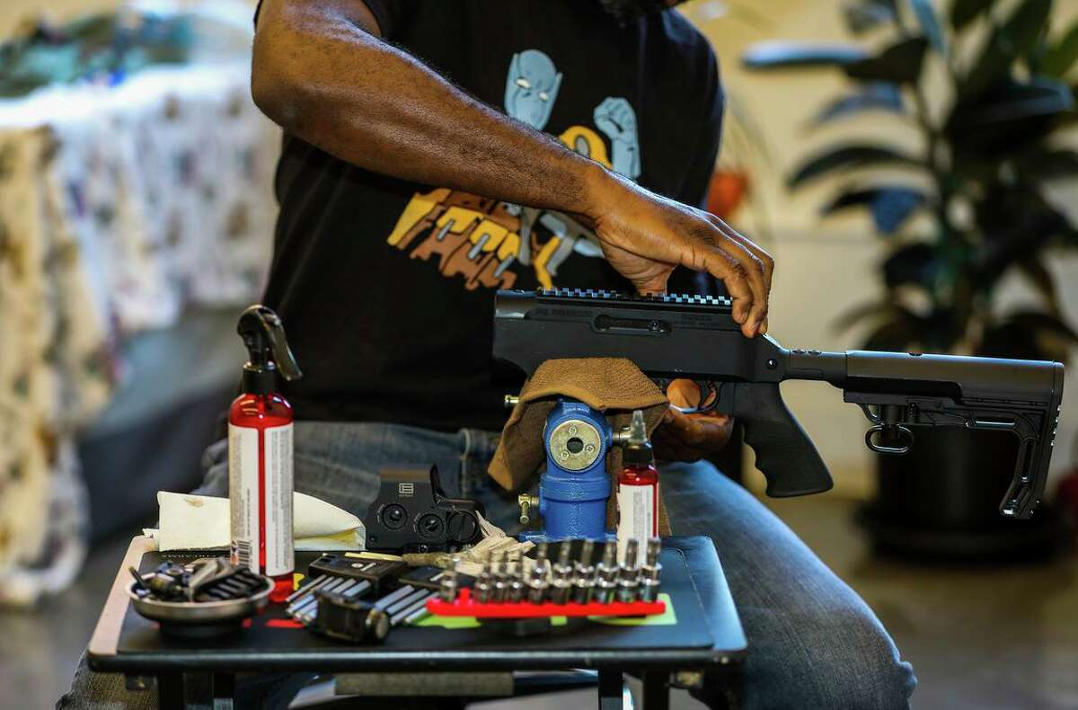 Anthony Dart cleans his rifle in his studio on Friday, June 11, 2021, in Oakland, Calif. The 42-year-old firearms safety instructor says Black Americans face more barriers to exercising their Second Amendment rights than white Americans do.