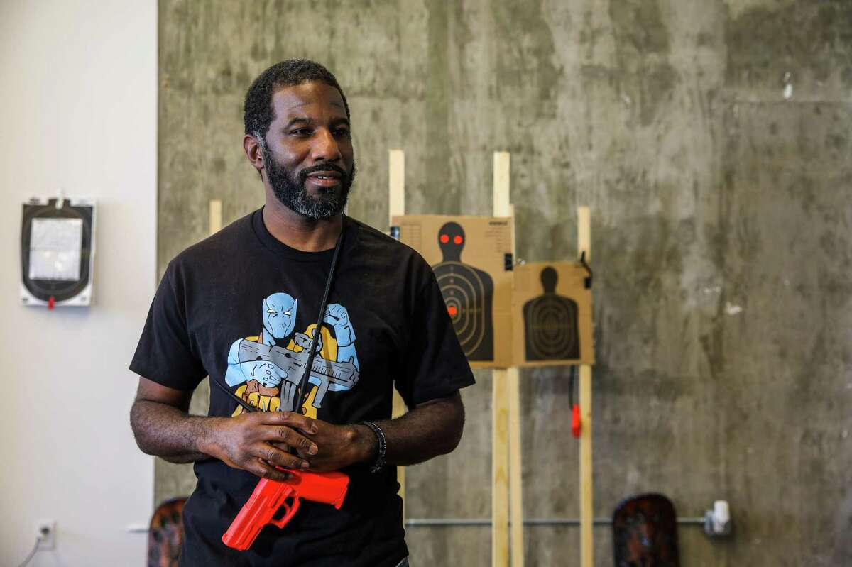 Anthony Dart, a 42-year-old Oakland transplant by way of Vicksburg, Miss., brought his enthusiasm for hunting and shooting to the heart of Fruitvale. Here Dart holds an orange demo gun as he speaks with The Chronicle on Friday, June 11, 2021, in Oakland, Calif. Dart teaches shooting self-defense classes for real-life scenarios -- such as home invasion robberies -- and views guns as a form of empowerment.