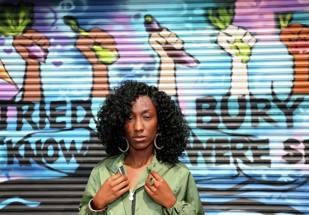 Keisha Henderson stands in front of a mural located outside the Handy Market in East Oakland on Friday, Aug. 6, 2021, in Oakland, Calif. The 29-year-old violence prevention activist has been helping to paint the mural on the corner store at the end of her block with a group called the Bay Area Mural Program.