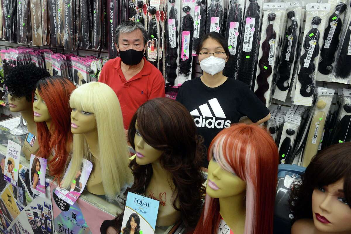 Owner Charlie Yu poses with employee Hui Zhang behind the counter at JB Beauty Supply, in Bridgeport, Conn. Aug. 11, 2021. Yu said he and his employees will continue wear masks in their downtown wig and beauty accessory store and will ask that customers do the same following the city's new executive order that went into effect on Wednesday.