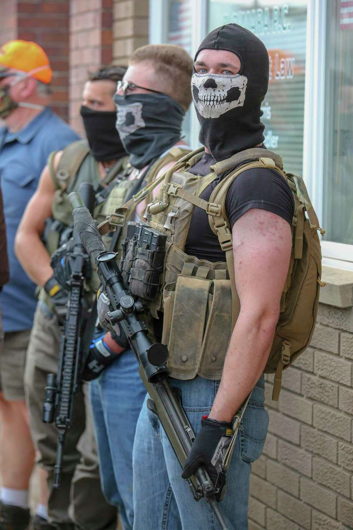 The Base members Thomas Denton, Tristan Webb and Justen Watkins stand with firearms across from the Huron County Building during a Black Lives Matter demonstration in Bad Axe last year. (Eric Young/Tribune File Photo)