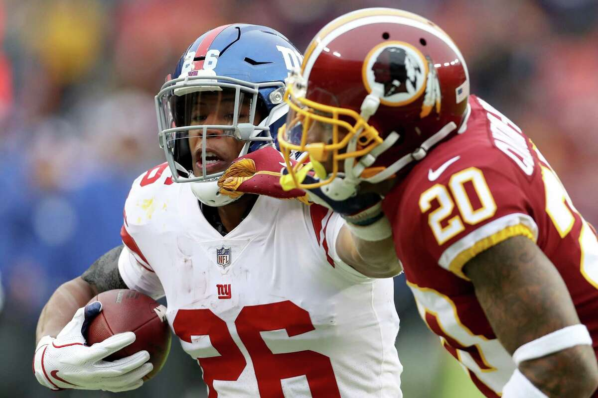 LANDOVER, MARYLAND - DECEMBER 09: Running back Saquon Barkley #26 of the New York Giants stiff arms strong safety Ha Ha Clinton-Dix #20 of the Washington Redskins in the first half at FedExField on December 09, 2018 in Landover, Maryland. (Photo by Rob Carr/Getty Images)