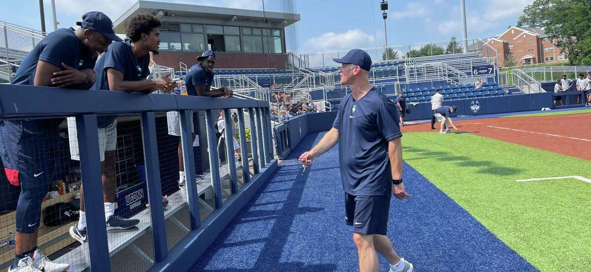 UConn basketball coach Dan Hurley approaches the dugout and chats with players during the program's softball game Wednesday at Burrill Family Field.