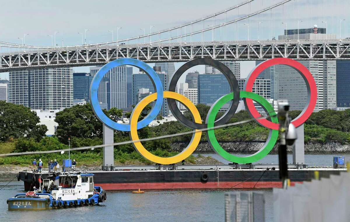 Workers prepare to remove the Olympic rings floating in the water after the 2020 Summer Olympics ended on Aug. 8, in Tokyo, Wednesday, Aug. 11, 2021. (Kyodo News via AP)