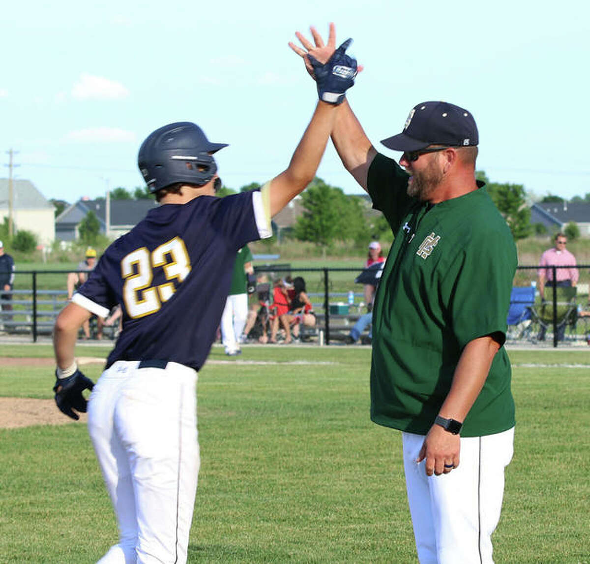 Father McGivney coach Chris Erwin (right) greets Jacob McKee rounding third base after McKee's home run in a regional championship victory over Metro-East Lutheran on June 7 in Glen Carbon.