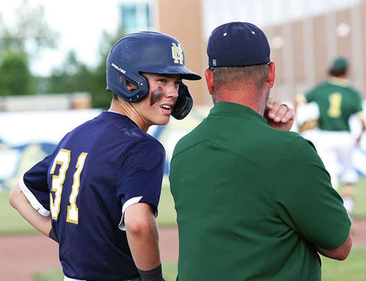 Father McGivney's Jackson Rodgers (left) listens to coach Chris Erwin at third base during a break in play of a game last season in Glen Carbon.