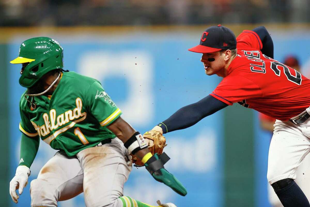 CLEVELAND, OH - AUGUST 10: Josh Harrison #1 of the Oakland Athletics is tagged out stealing second base by Ernie Clement #28 of the Cleveland Indians in the sixth inning at Progressive Field on August 10, 2021 in Cleveland, Ohio. (Photo by Ron Schwane/Getty Images)