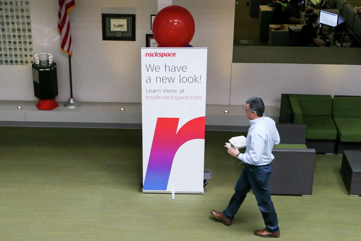 """A Racker carries lunch while walking in front of a sign with Rackspace's logo, a gradient """"r,"""" on Wednesday, March 6, 2019."""
