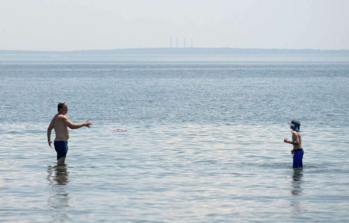 Folks wade in the water on the beach at Greenwich Point Park in Old Greenwich, Conn. Wednesday, June 30, 2021. Locals flocked to the Tod's Point beach Wednesday as high temperatures rose into the mid-90s.