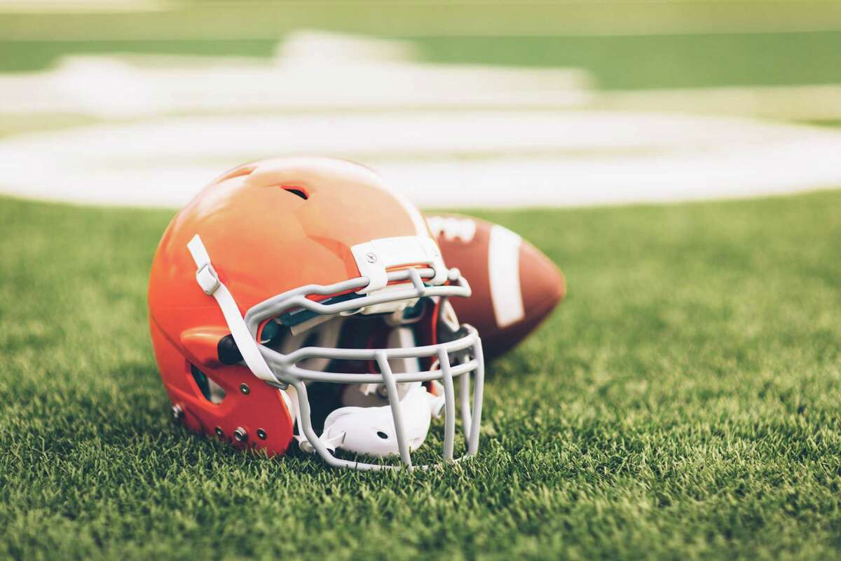 An American Football helmet sits with a football on a football playing field. The light is from the sun which is about to set, shallow depth of field. Copy space included. Sport background image.
