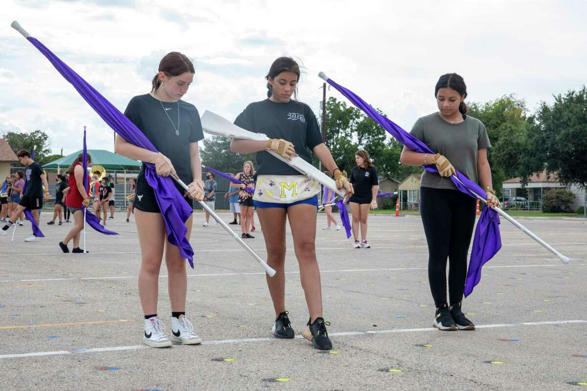 Sophomore Hailey Martinez, left, color guard captain senior Isabel Sanchez Pena, center, and sophomore Natalia Balderas work on marching techniques during Midland High's marching band practice Wednesday, Aug. 11, 2021 at Midland High School. Jacy Lewis/Reporter-Telegram