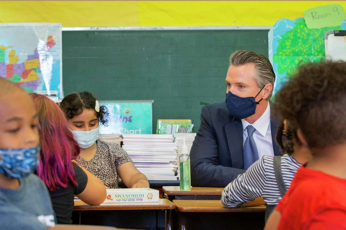 California Gov. Gavin Newsom visits Carl B. Munck Elementary School, Wednesday in Oakland, Calif. The governor announced that California will require its 320,000 teachers and school employees to be vaccinated against the novel coronavirus or submit to weekly COVID-19 testing.