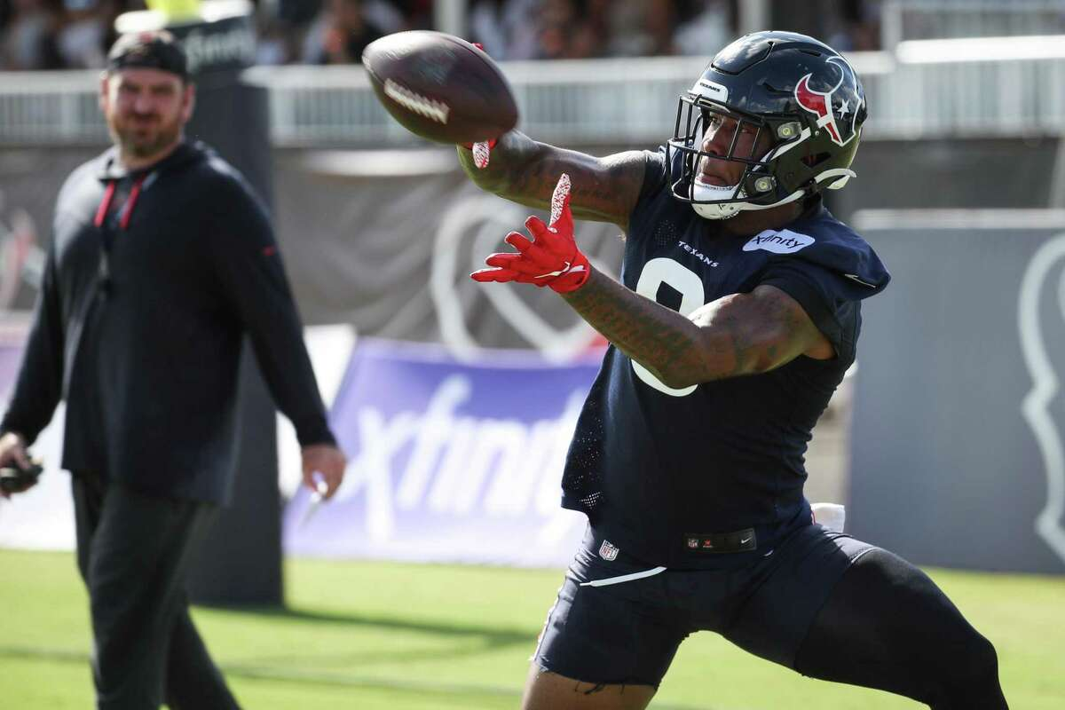 Houston Texans tight end Brevin Jordan (9) makes a catch in front of offensive coordinator Tim Kelly during an NFL training camp football practice Saturday, July 31, 2021, in Houston.