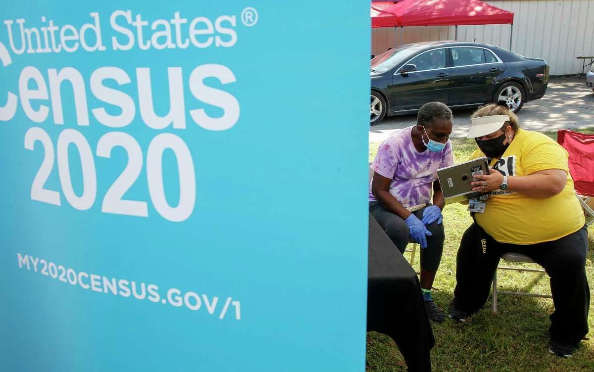 Elizabeth Lastovica, right, helps Helen London, 70, fill out the Census during a COVID-19 testing and food distribution event hosted by Rep. Sheila Jackson Lee at St. Paul Missionary Baptist Church on Saturday, Oct. 10, 2020, in Houston.