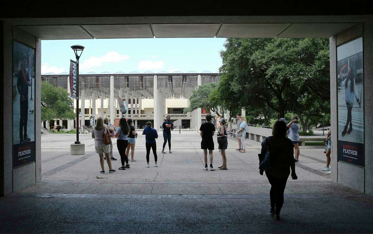 A UTSA ambassador takes visitors on a tour of the campus. The university is delaying the start of in-person classes by three weeks, moving them online.