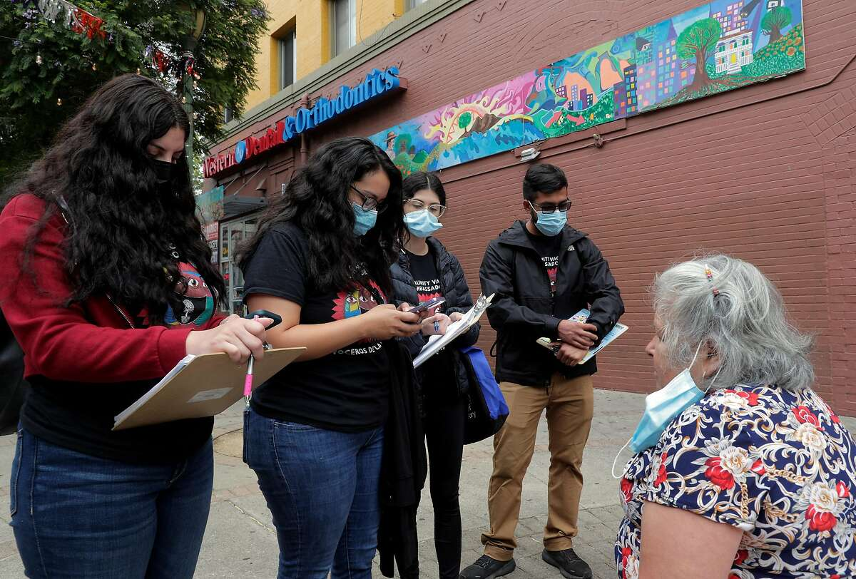 L-R, Alexa Rivas, Raquel Marquez, Carolina Quintero, and Efrain Trujillo look up a vaccination site for Evangelina Nieves, seated, while they help local residents with vaccination resources in the Fruitvale district of Oakland, Calif., on Thursday, August 5, 2021. As the DELTA variant surges in California, Latinos continue to suffer disproportionately. A new effort by the Unity Council and UCSF is targeting the Fruitvale district to bring vaccine information to residents.