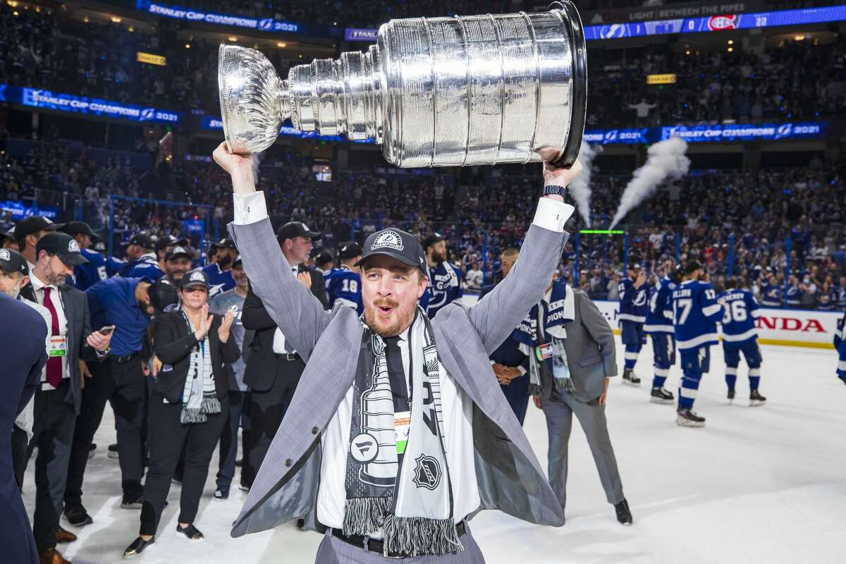 Brian Garlock, Video Coordinator of the Tampa Bay Lightning hoists the Stanley Cup overhead after the Tampa Bay Lightning defeated the Montreal Canadiens in Game Five to win the best of seven game series 4-1 during the Stanley Cup Final of the 2021 Stanley Cup Playoffs at Amalie Arena on July 7, 2021 in Tampa, Florida.