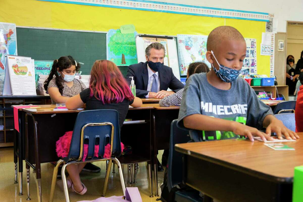 Gov. Gavin Newsom sits among students at Carl B. Munck Elementary School in Oakland.