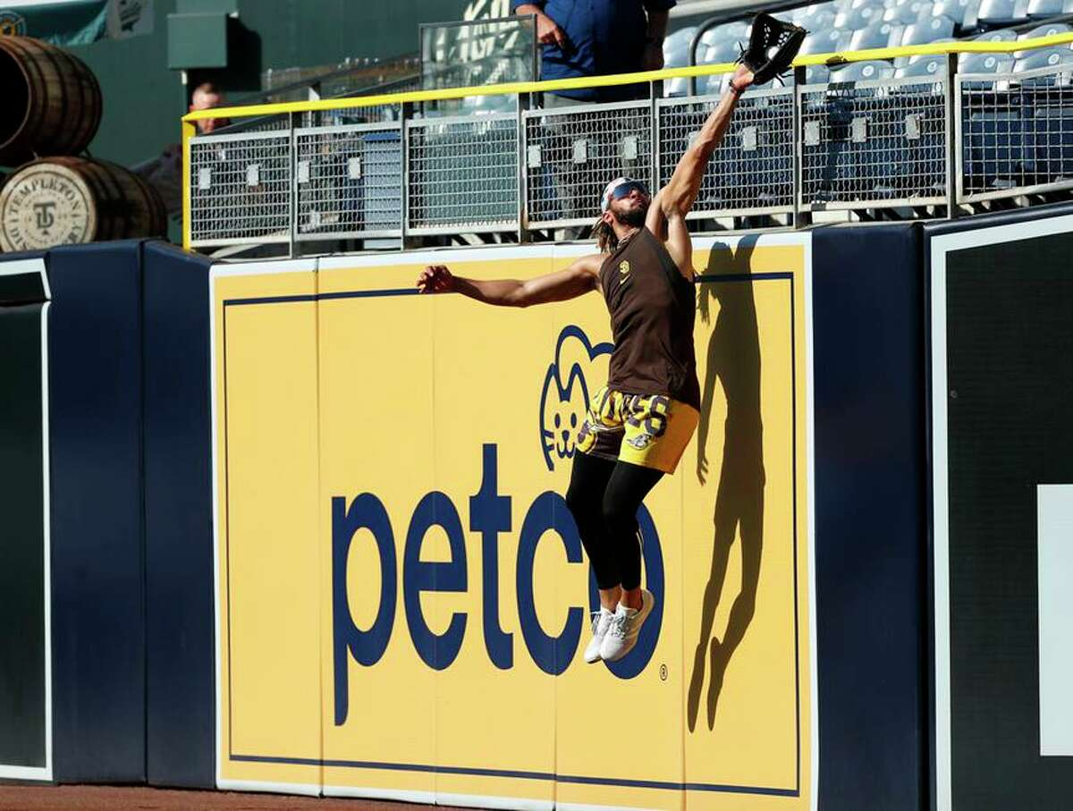 The Padres' Fernando Tatis Jr. catches a ball against the right-field wall during practice at Petco Park on Monday.
