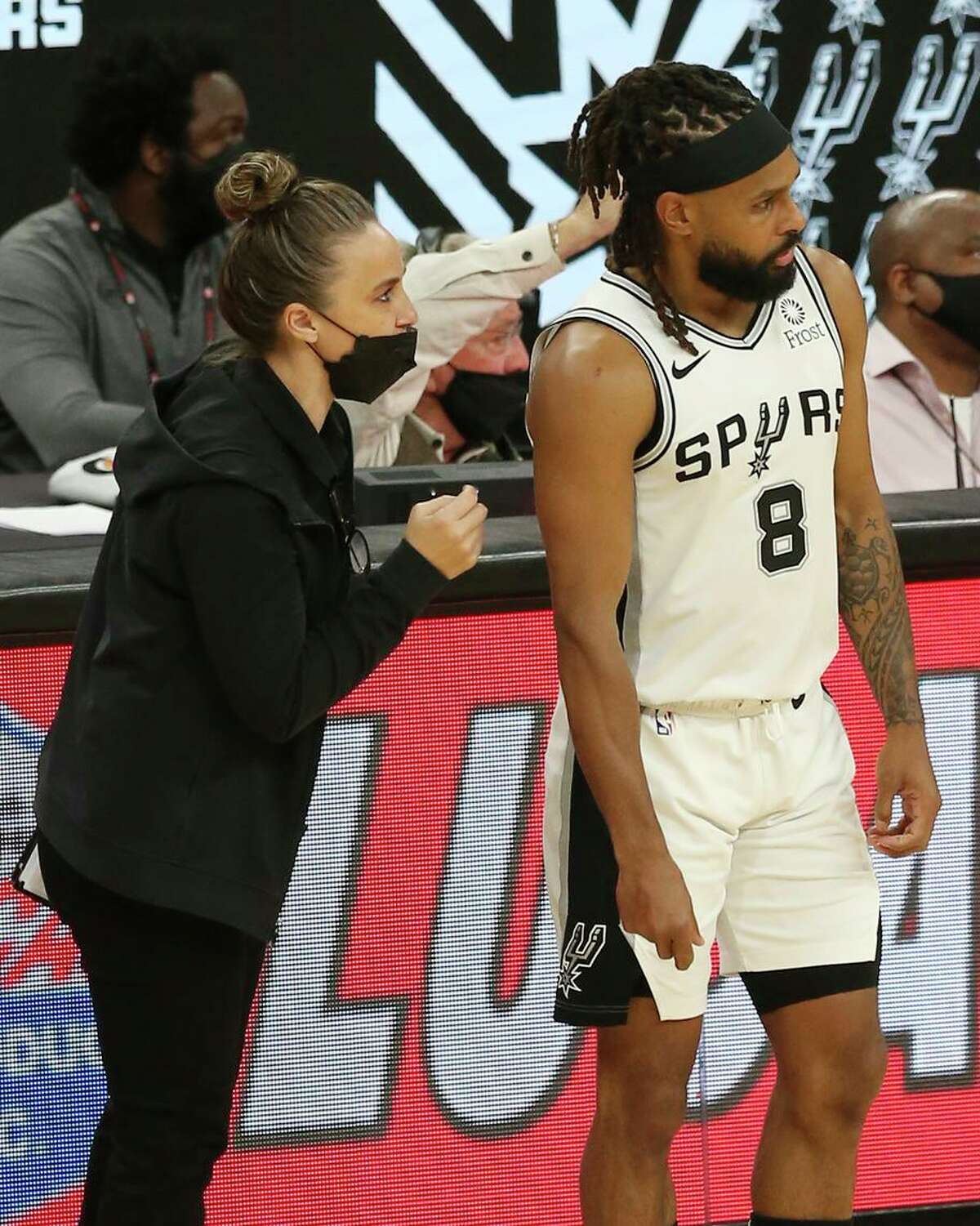 Spurs assistant coach Becky Hammon talks with Patty Mills. She has been interviewed for several head-coaching openings.