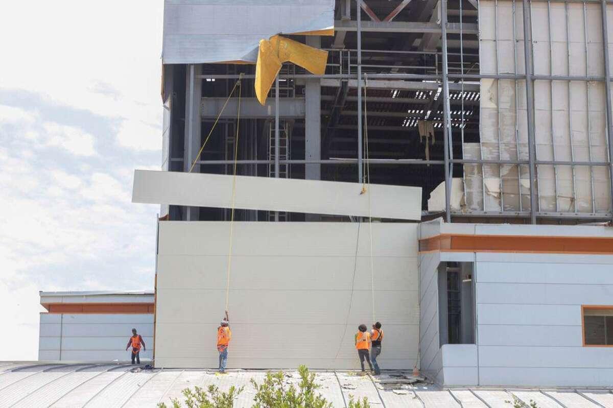 Trabajadores colocan láminas especiales en la fachada del Centro Cultural Nuevo Laredo que fue dañado durante la tormenta de mayo pasado.